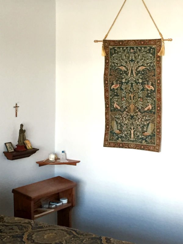 Mille fleurs tapestry hanging in a bedroom