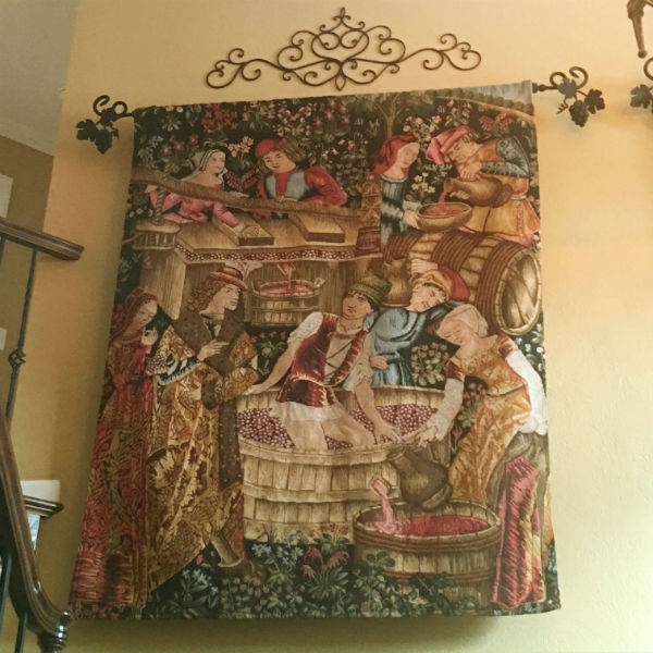 Pressing the Grapes tapestry hanging in a home